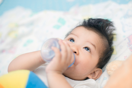 Beautiful little baby with a milk bottle in bed Stock Photo