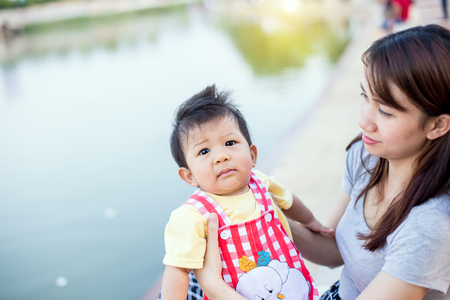 Portrait of a crying little boy who is being held by her mother Stock Photo