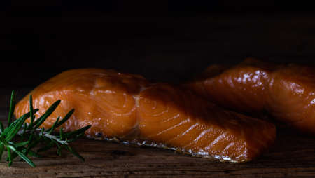 Smoked Salmon two pieces in wooden dark background