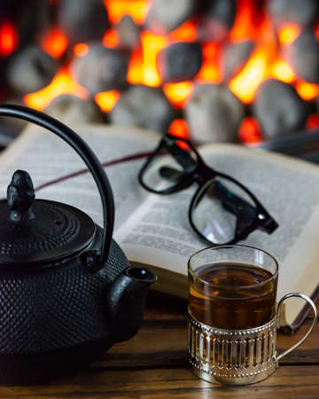 Cup of tea and open book in front of warm fireplace. Stock Photo