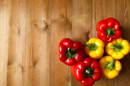 Red bell peppers on the wooden background