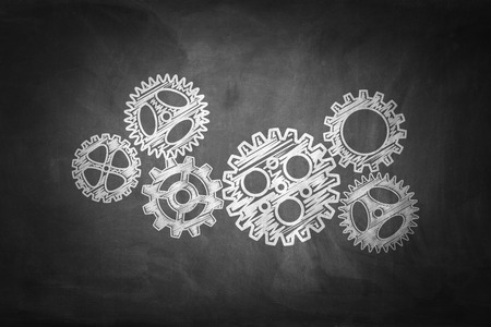 Business concept: Gears on chalkboard background.