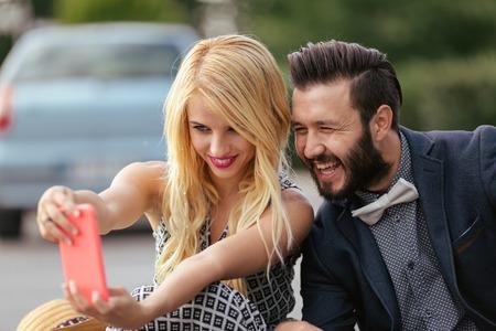 self   portrait: Couple taking self portrait on a smart phone Stock Photo
