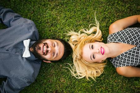 femme romantique: Heureux jeune couple allong� sur l'herbe
