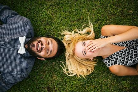 jovenes felices: Feliz pareja joven tumbado en la hierba