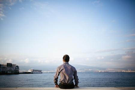 soledad: Joven hombre sentado mirada en el mar - Soledad.