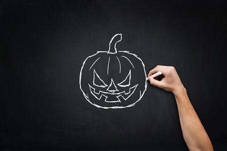 jack o' lantern: Smiling jack o lantern drawing on blackboard. Stock Photo