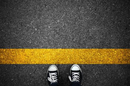 Mensen bij een beginnend gele lijn op asfalt. Stockfoto