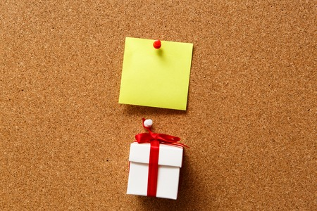 corkboard: Adhesive Note and Christmas gitf box on corkboard.