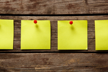 pinning: Adhesive notes pinning on wooden wall. Stock Photo