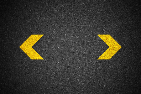 Yellow arrow sign on asphalt Stock Photo