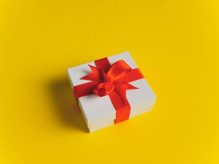 White gift box tied with red ribbon on yellow background