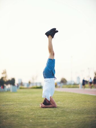 Man doing yoga outdoor. Young man practicing yoga fitness exercise