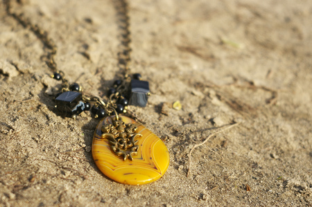 Handmade. Necklace on the sand on unny day Banco de Imagens