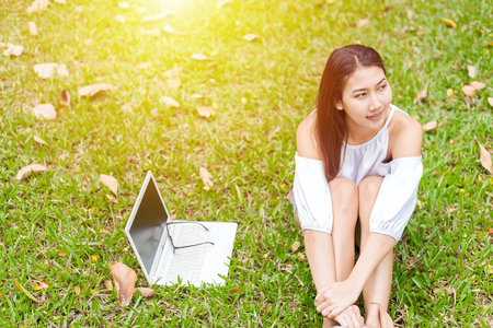 A girl sitting on the grass and labtop near her. A glasses is on the labtop. Stock Photo
