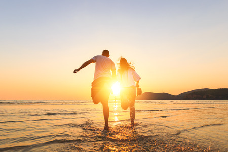 couple running and hand hold on the beach between sunset. Archivio Fotografico