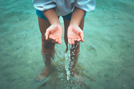 women stand in the water and hands fetch water and have water splash.