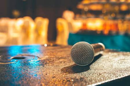 Microphone on the ground and blurred photo of conference hall or seminar room or wedding room background. Standard-Bild - 116420954