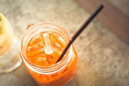 Iced Thai milk tea in glass on the table. Stock Photo