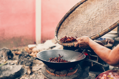 chillies in threshing basket and people pour it in to the cooking pan. 免版税图像