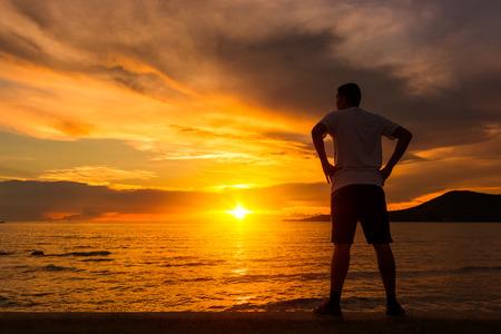 Jeune homme sportif faisant des étirements après une course à la plage