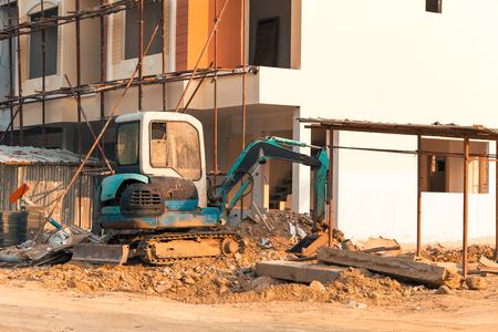 Mini excavator on construction site.Excavator regulates the terrain around the house. Banco de Imagens
