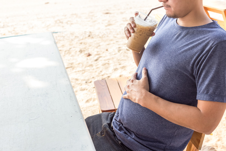 A fat man and big belly drink coffee .