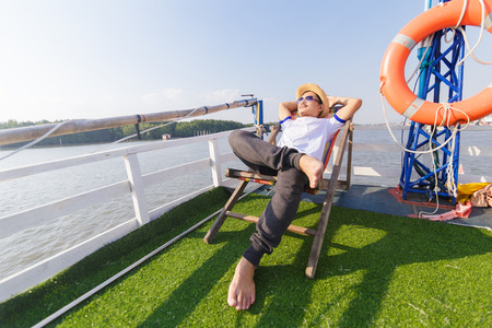 a man wear hat and sunglasses. He lie on sunbeds in the cruise ship. 写真素材