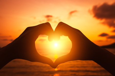 hands forming a heart shape with sunset silhouette.