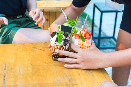 waitress serving the ice cream chocolate, ice cream strawberry   and ice cream tea to customers.
