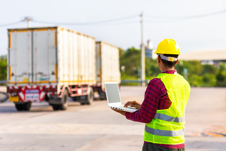 Foreman use computer for test and checking vehicle at industry. Working concept.
