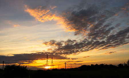Mobile phone communication antenna tower with silhouette in sunset sky background