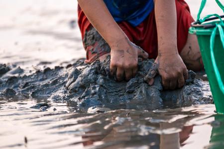 Hands dig sand and mud for find sea shell. Reklamní fotografie