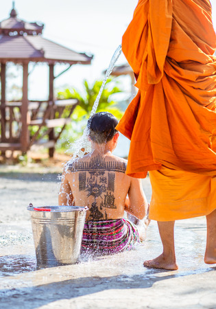 Chachoengsao , Thailand - March 6 , 2019: A monk pour water to a man for remove one's bad luck with a ceremony.