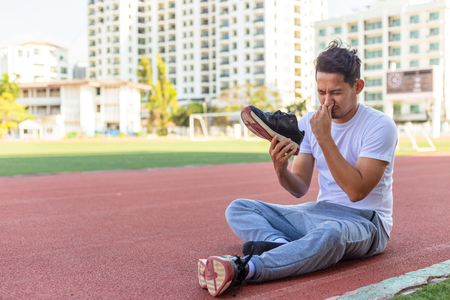a man disgusted by the smell of his running shoe. A sport man sitting on the  track race at stadium. Stockfoto