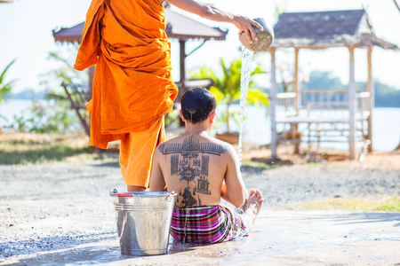 A monk pour water to a man for remove one's bad luck with a ceremony. Stockfoto