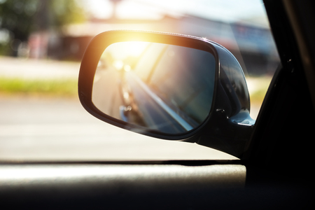 Reflection of a car on the road  in a car side mirror and sunset. Фото со стока