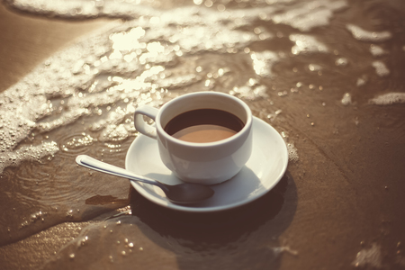 hot cup of coffee on  sand in the beach and sea water flow. Standard-Bild