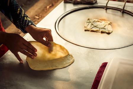 Hands of street vendor cooking Thai style sweet roti. Enjoy street food.