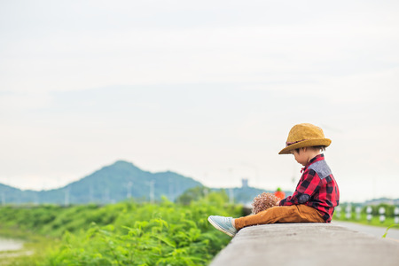 A children wear hat and sitting on the ground and flower near him. The reservoir and mountain.
