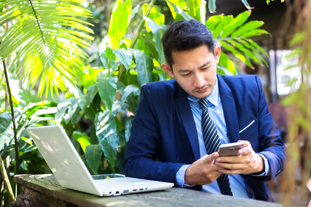 Businessman using mobile smart phone and working on laptop computer. 写真素材 - 122673084