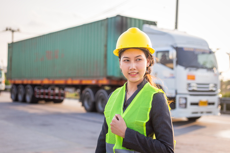 Asian woman engineer check for control loading Containers box from Cargo freight ship for import and export Stock Photo
