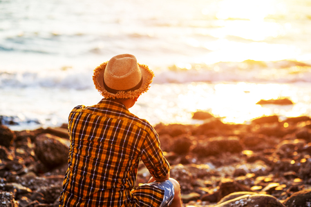 A man travel and  sitting on the stone near sea water and sunset in summer. 写真素材 - 122674590