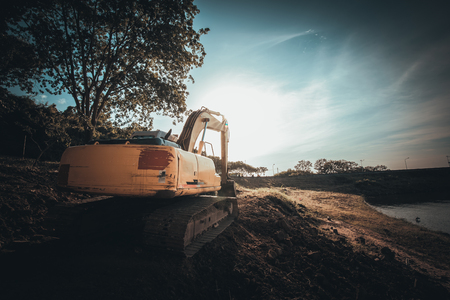 The orange backhoe is on the ground with sunset. 写真素材 - 122674591