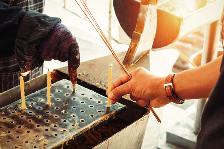 ็Hand hold candle and incense at temple.