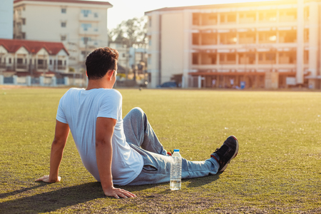 Thirsty man on grass at sport stadium after exercise. A bottle of pure water on grass near a man. Imagens