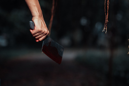 Woman holding knife with blood in the forest, halloween concept 写真素材 - 122677662