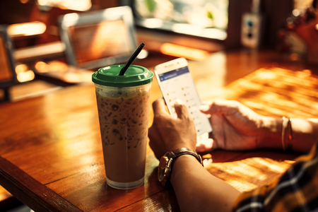 Ice coffee is on the table near hands use mobile phone at summer in coffee shop.