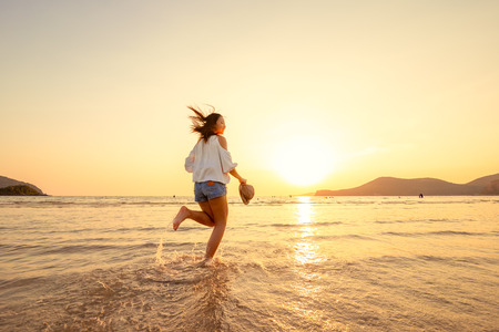 A woman running in to the beach. Woman happy with vacation summer on the beach and sunset.