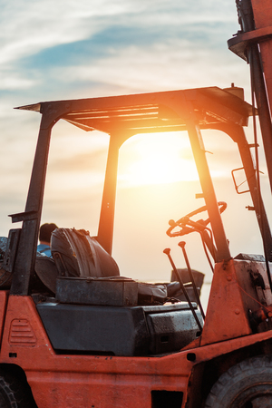 Old Forklift transporting cargo on a road near the sea with sunset time.